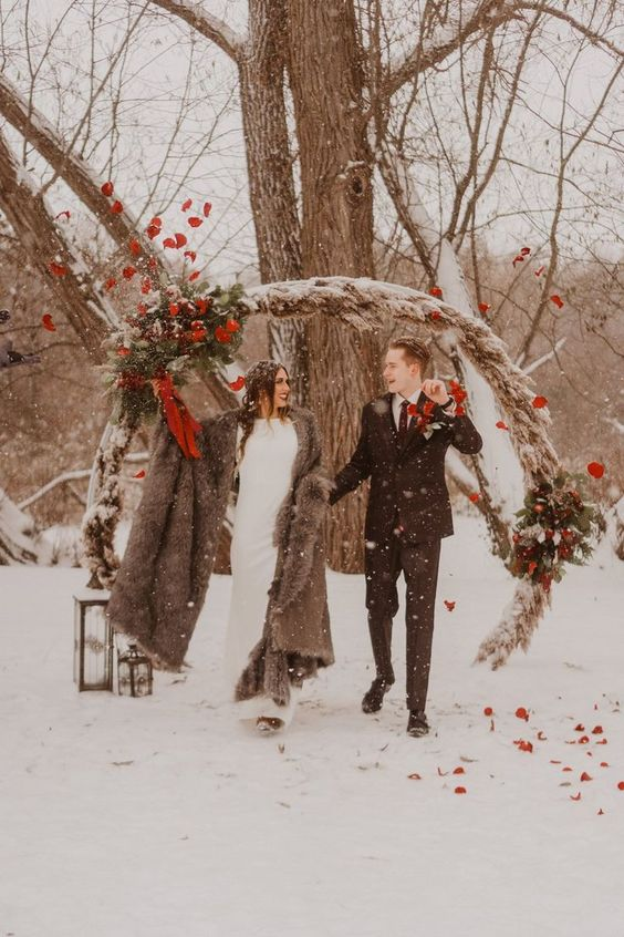 a round pampas grass wedding arch with greenery, bright blooms and red ribbons and pinecones for a winter woodland wedding