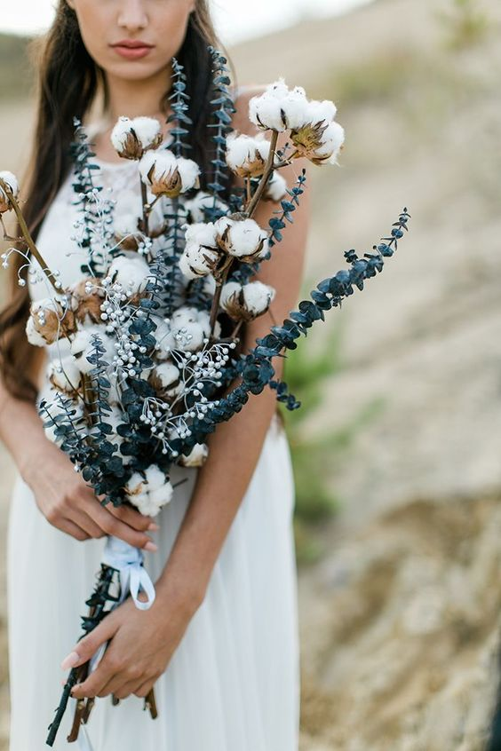 a simple boho woodland wedding bouquet with cotton branches, berries and eucalyptus is a lovely idea