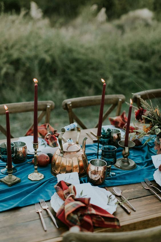 a simple fall mountain wedding tablescape with a blue runner, burgundy candles, chcked napkins and fruits on the runner