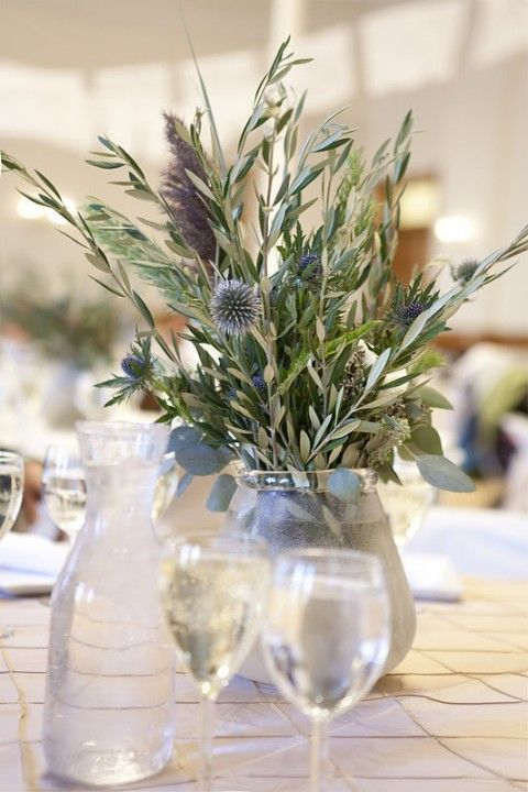 a simple wedding centerpiece of olive greenery, thistles allium, thistles and some dried herbs for a natural wedding