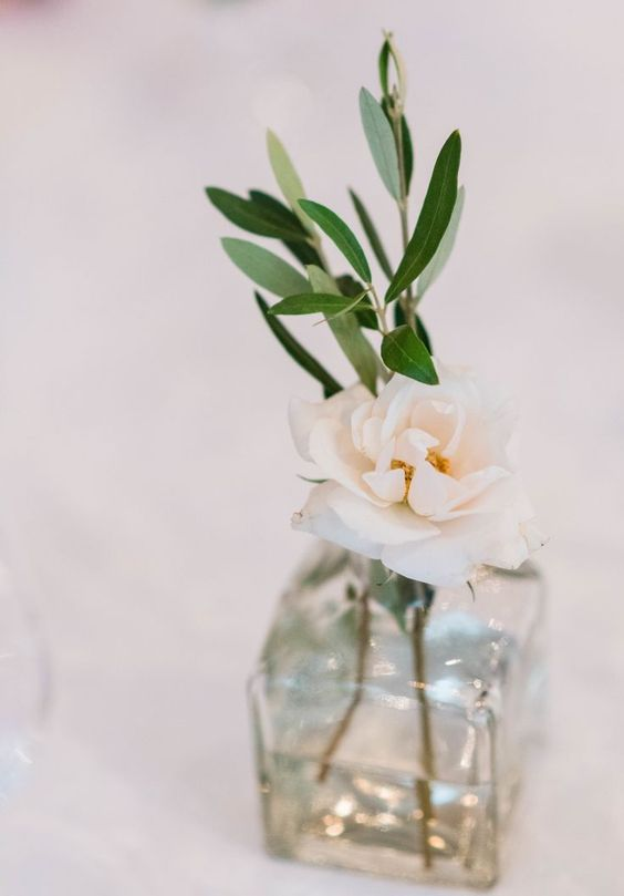 a square bottle with olive greenery and a blush rose is a romantic and cute wedding centerpiece