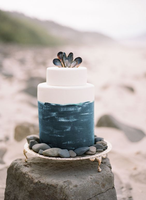 a statement beach wedding cake with navy brushstrokes and mussel shells on top for a beach wedding