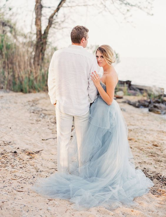 a strapless layered light blue wedding dress with a train for a bride at a blue beach or coastal wedding
