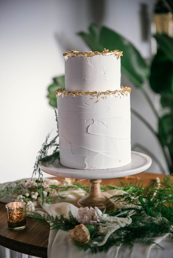 a stylish white textural wedding cake with gold glitter is a lovely and very refined idea for a modern wedding
