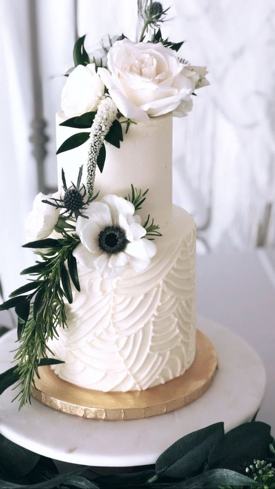 a stylish white wedding cake with a textural tier, sugar and fresh blooms and greenery is very refined