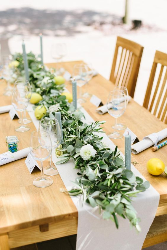 a summer wedding tablescape with eucalyptus, olive, white blooms, lemons and grey candles for a bright look