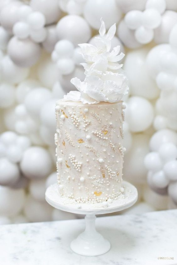 a tall neutral wedding cake decorated with edible pearls and beads and with white sugar blooms on top