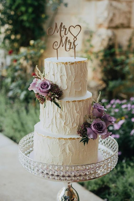 a textural neutral wedding cake with gold leaf, purple blooms and greenery and a calligraphy topper