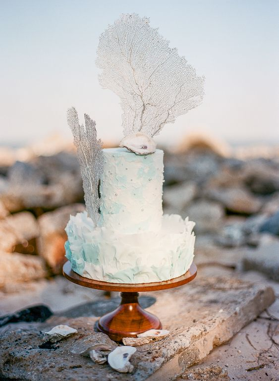 a textural white and turquoise wedding cake decorated with pearls, corals and a seashell on top