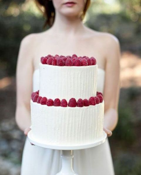 a textural white wedding cake topped with fresh raspberries is a delicious and lovely dessert idea for a wedding