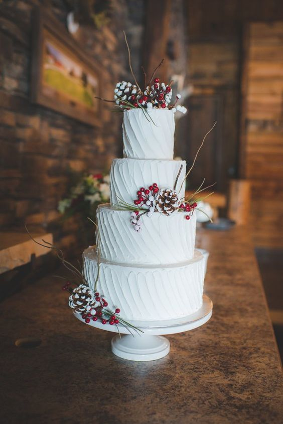 a textural white wedding cake with snowy pinecones, berries and twigs is a lovely rustic dessert idea