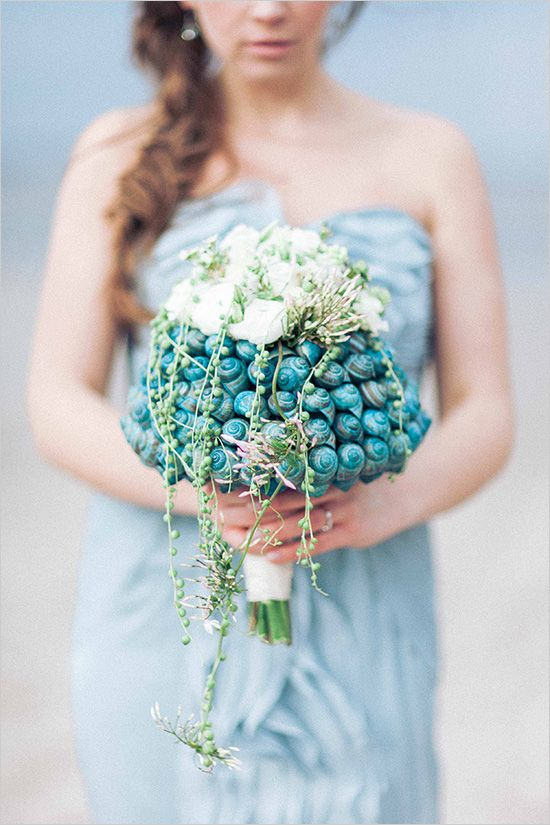a unique beach wedding bouquet made of blue seashells, some white blooms and cascading greenery