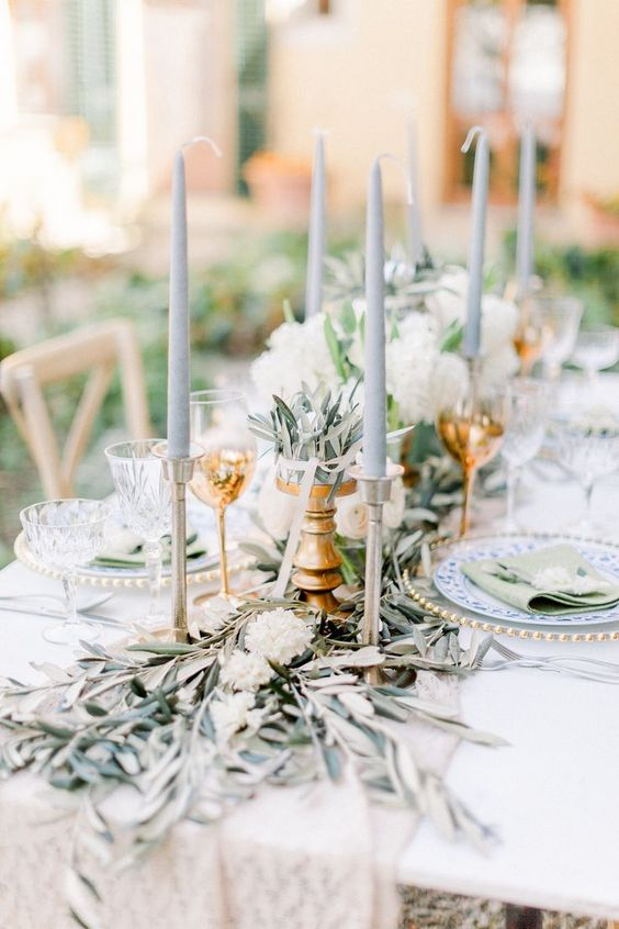 a wedding tablescape with olive branches, white blooms, grey candles is a very elegant and chic idea