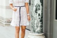 a white lace off the shoulder mini dress with statement earrings, a navy sash and nude heels for a hot summer look