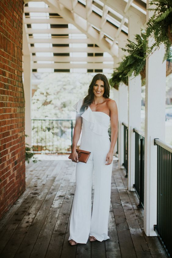a white one shoulder ruffle strap jumpsuit with wideleg pants and a small brown leather clutch compose an elegant modern look