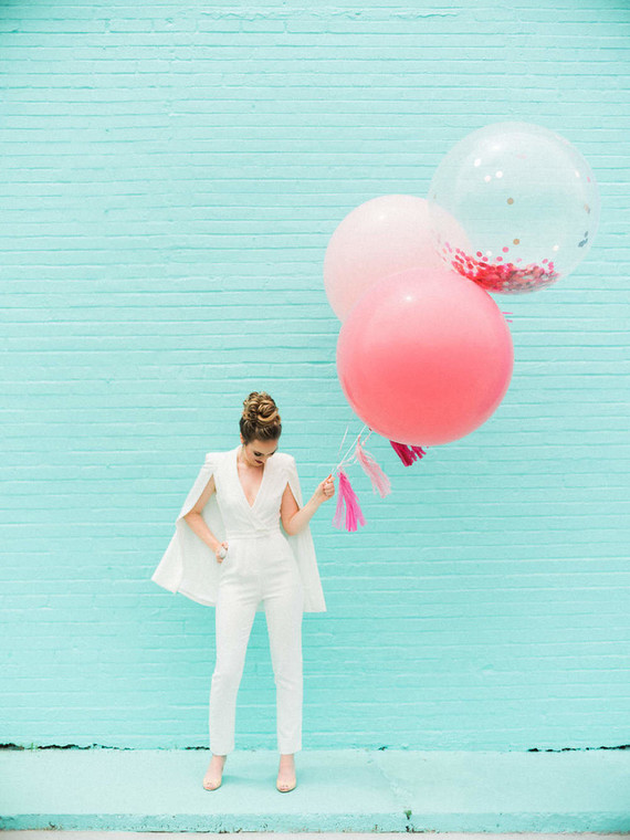 a white plain jumpsuit with a deep neckline and a cape, nude shoes and a top knot for a modern bride-to-be