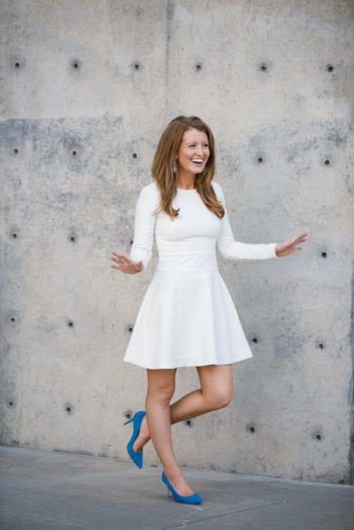 a white plain midi dress with a fit and flare skirt, long sleeves, a high neckline and blue heels for a modern bride to be