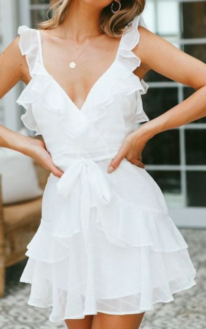 a white ruffle mini dress with a deep neckline, a sash with a bow and a statement necklace is a cute idea for a summer bride to be