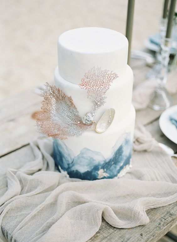 a white wedding cake with blue watercolors, corals and a seashell with pearls for a beach wedding