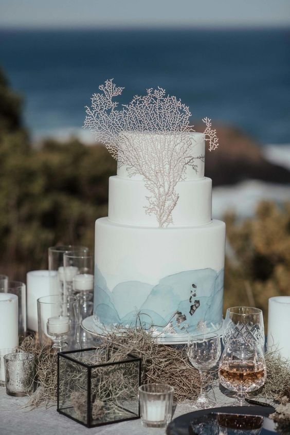 a white wedding cake with blue watercolors, silver foil and corals for a blue beach wedding