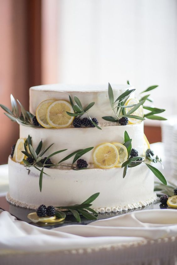 a white wedding cake with citrus slices, blackberries and olive greenery for a fresh and bold look at the wedding