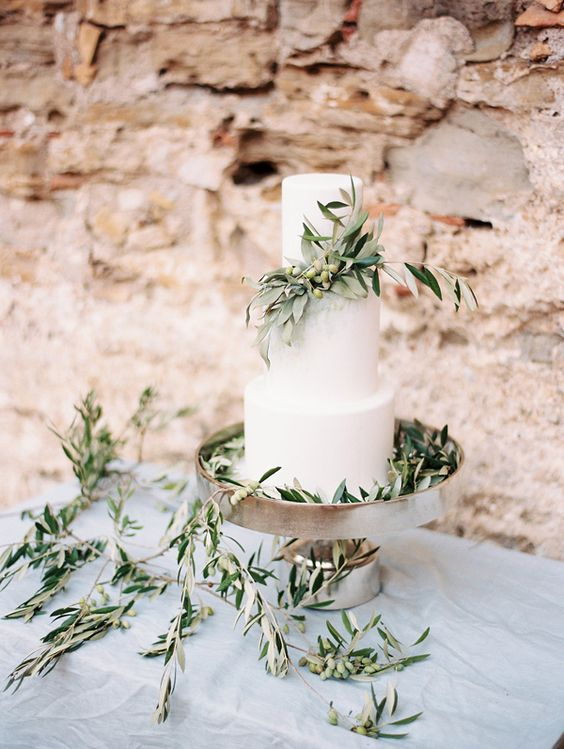 a white wedding cake with olive branches and olives is an ideal thing for a natural wedding or a rustic one