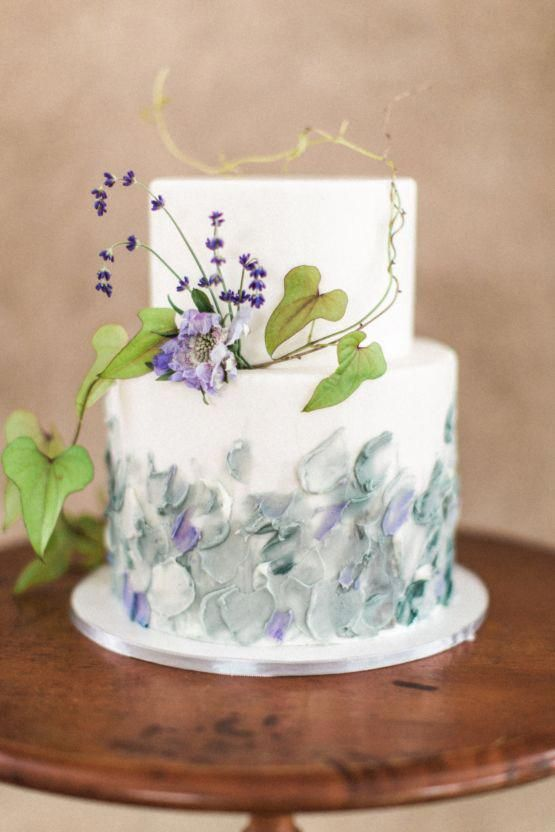 a white wedding cake with textural pastel decor and fresh purple blooms and leaves for a spring or summer wedding