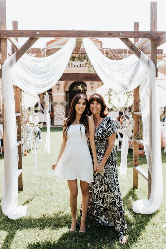 a whte plain midi dress with a ruffle neckline and skirt plus nude heels for a summer bridal shower