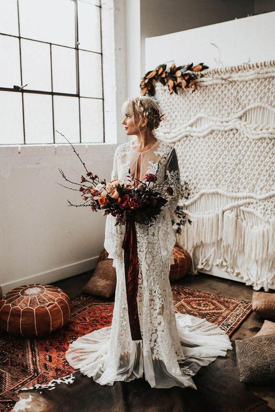 a woodland boho bride in a gorgeous boho lace wedding dress with bell sleeves and a train, a boho macrame wedding backdrop