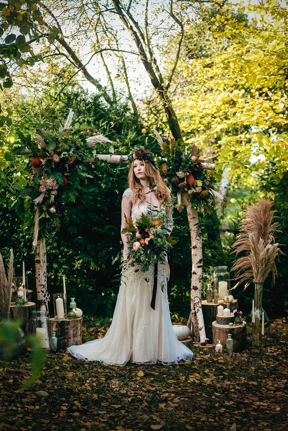 a woodland boho wedding arch of branches, greenery and foliage, bright blooms, pampas grass and candles on tree stumps