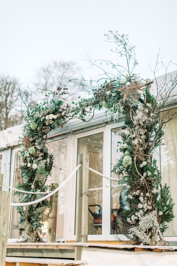 a woodland boho wedding arch of greenery, foliage, green and dried blooms, twigs, branches and moss looks wild