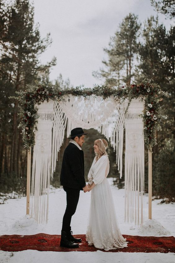 a woodland boho wedding arch with macrame, greenery and white blooms is a lovely idea for a woodland wedding