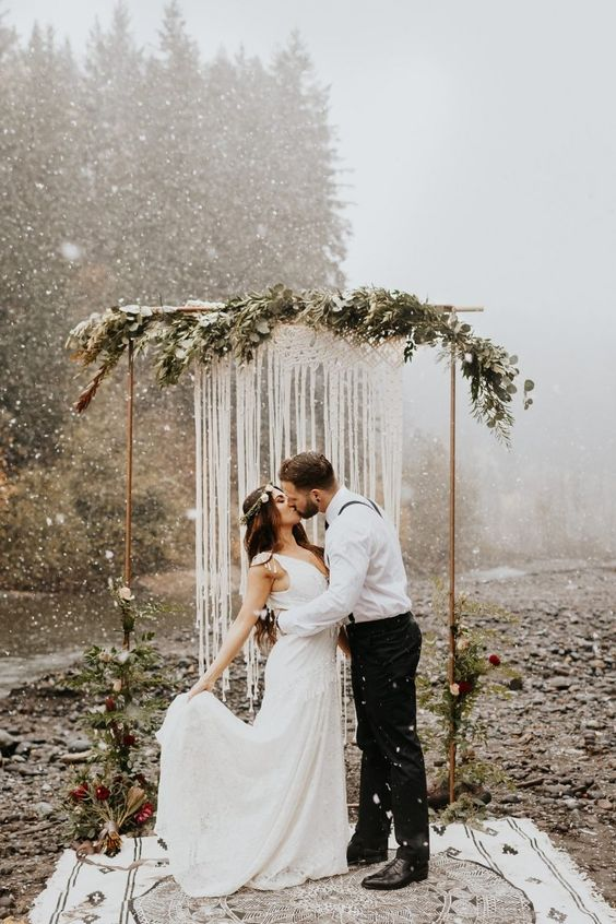 a woodland boho wedding arch with much greenery, bold blooms and a macrame hanging plus a boho rug is a lovely idea