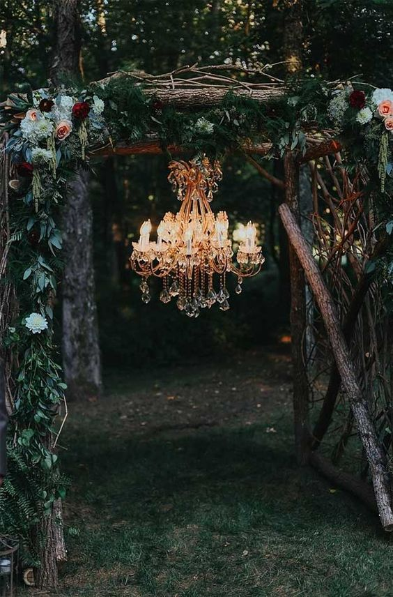 a woodland wedding arch of branches and sticks, greenery, neutral and bright blooms and a crystal chandelier to light it up