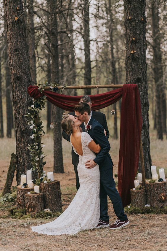 a woodland wedding arch of branches, greenery, a burgundy velvet curtain and with candles on tree stumps around