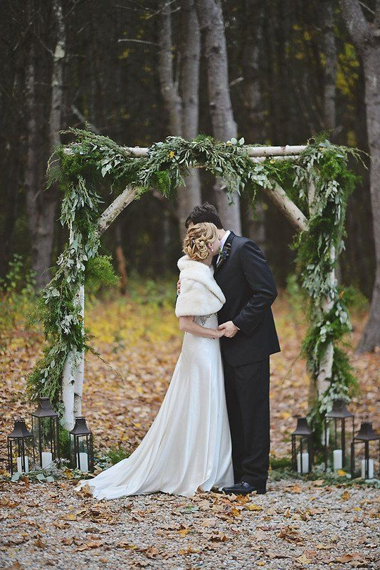 a woodland wedding arch with greenery and ferns, candle lanterns by its base is great for a fall or winter wedding