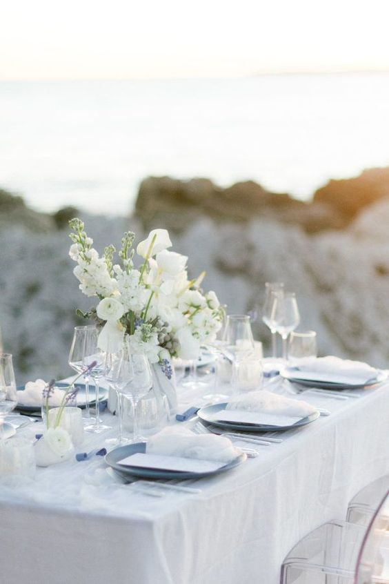an ethereal blue beach reception table with a white tablecloth and menus, with white and blue blooms and blue plates
