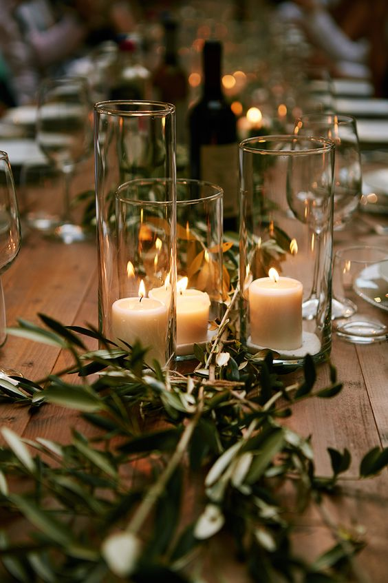 an olive greenery table runner, candles in hurrican candle holders make the table natural, rustic and fresh at the same time