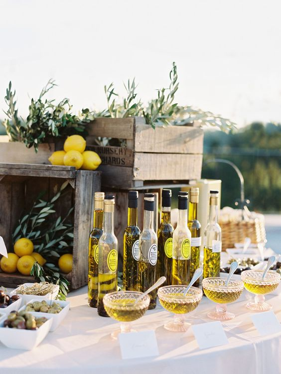 an olive oil tasting table with olive branches and lemons for decorating with a Mediterranean feel
