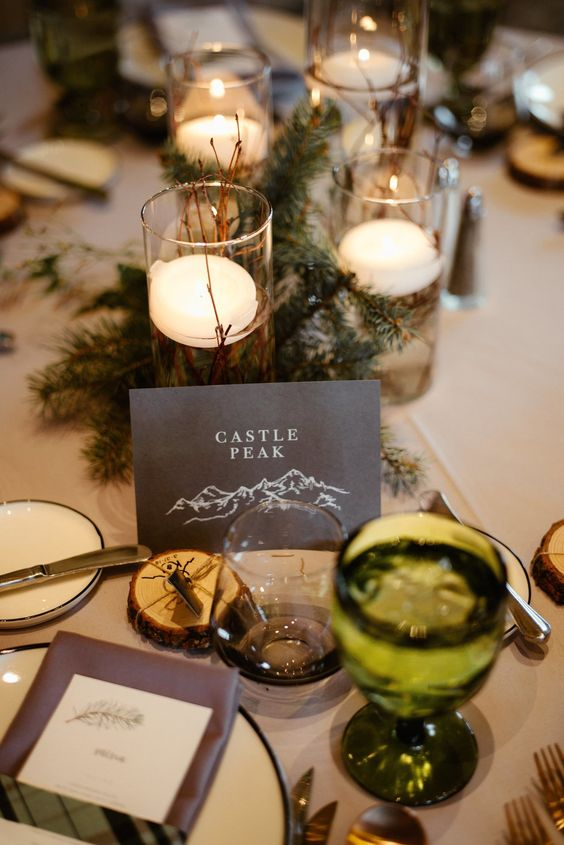 cool table decor with evergreens, a green glass, candles and twigs is great for a woodland or mountain wedding