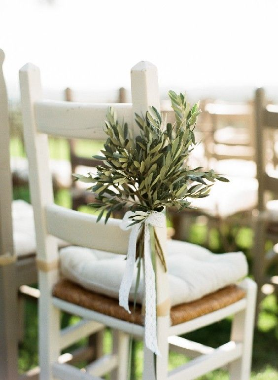wedding ceremony space chairs decorated with olive branch arrangements and bows look cute and simple