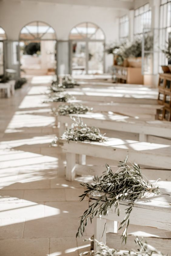 whitewashed benches decorated with olive branch bouquets is a great idea for a Tuscany wedding