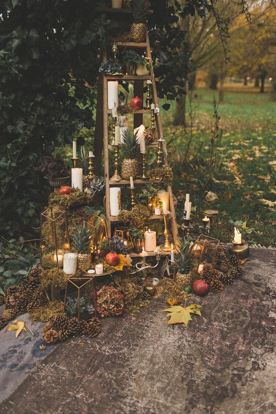 woodland boho and decadent wedding decor with gilded candleholders, gilded pineapples, pinecones, gall leaves and pomegranates