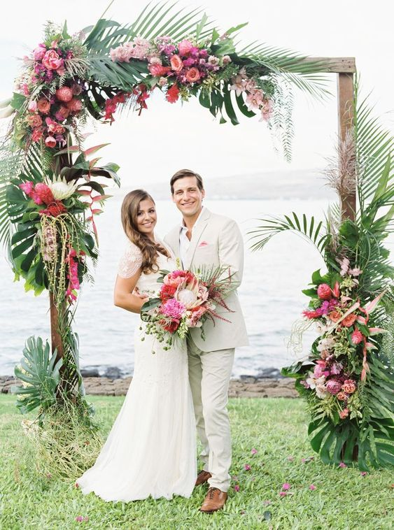 a bright tropical wedding arch topped with monstera leaves, pink, blush and purple blooms and cascading elements