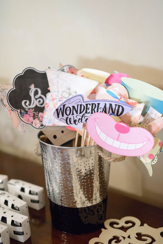 a bucket with Wonderland inspired wedding photo booth props in bold colors and arrows, smiles and more