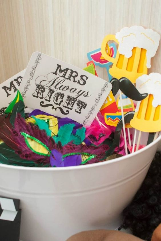 a bucket with props - signs, feather masks, glasses, moustache, beer and much more for a fun wedding