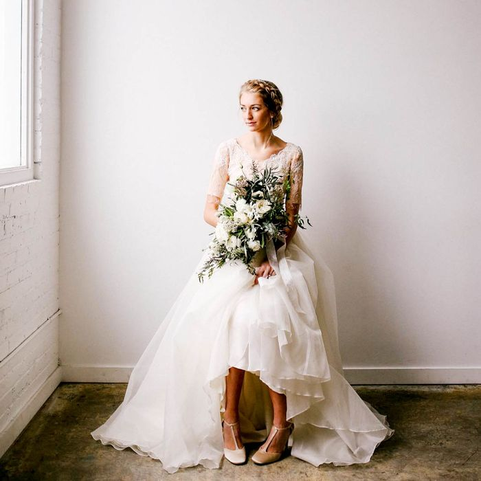 a charming high low wedding dress with a lace bodice with short sleeves and a layered tulle high low skirt plus nude shoes
