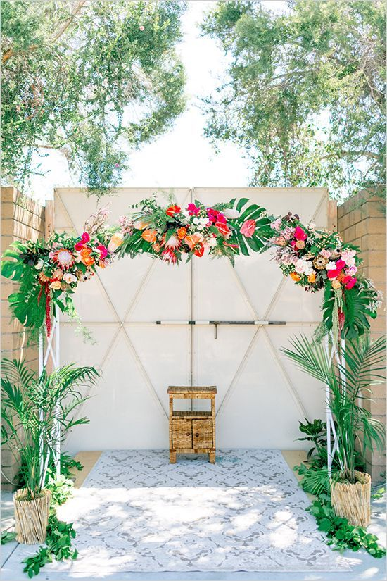 a cheerful and colorful tropical wedding arch decorated with leaves, pink, fuchsia and orange blooms