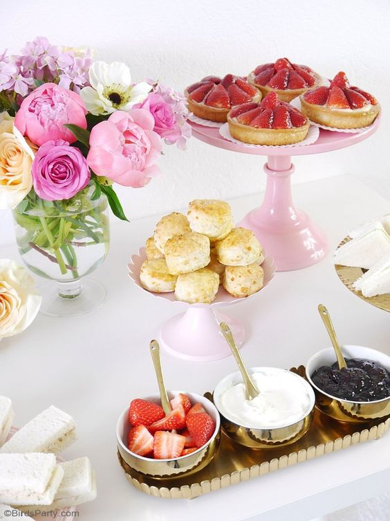 a chic dessert table with various sweets, dressings, berries and a floral centerpiece in a clear vase