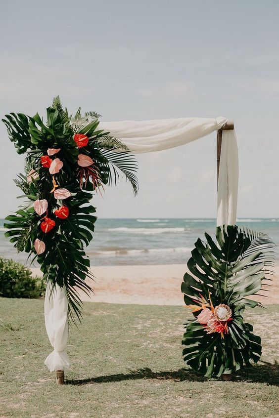 a chic tropical wedding arch of bamboo with white fabric, monstera leaves, pink and red flowers